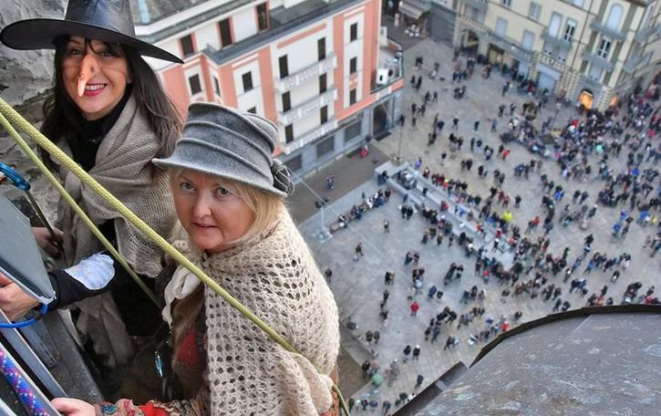 Sondrio, con il naso all'insù verso il campanile guardando la befana